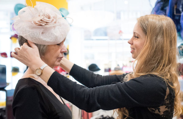 Beverley Edmondson fitting a hat on a millinery client.